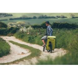 Frau mit Singletrailer steht auf Feldweg